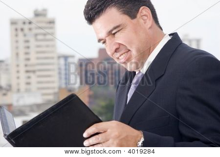 Portrait of a businessmann reading an inform at office poster