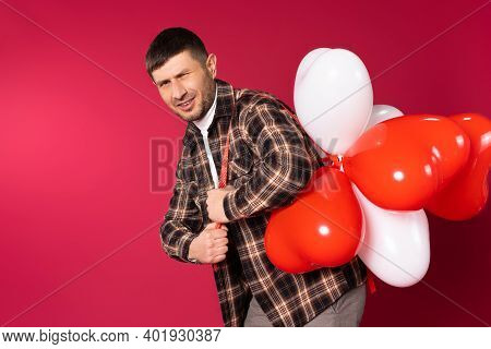 A Young Man Carries A Bunch Of Heart-shaped Balloons And Squints At The Camera. St.valentine's Day O