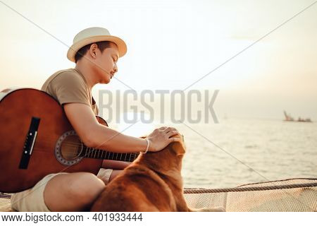 A Man Wear Straw Hat And Playing Guitar Music Song Near The Sea Sunset And Stroking The Head Dog Pet