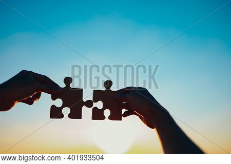 Two Hands Of Businessman To Join Jigsaw Puzzle Piece With Sky Background. Business Partnership, Team