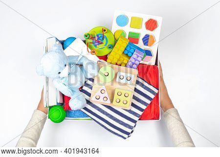 Donation Charity Concept. Hands Holding Donate Box With Clothes, Books, School Supplies And Toys On