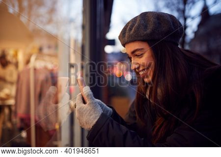 Evening View Of Woman Window Shopping Taking Picture Of Display In Fashion Store On Mobile Phone