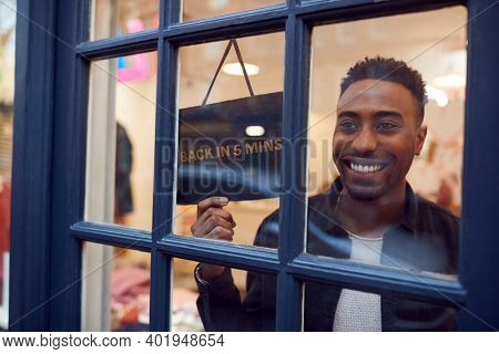 Smiling Small Business Owner Turning Around Back In 5 Minutes Sign On Shop Or Store Door