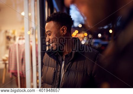 Evening View Of Two Men Window Shopping Looking At Display In Fashion Store