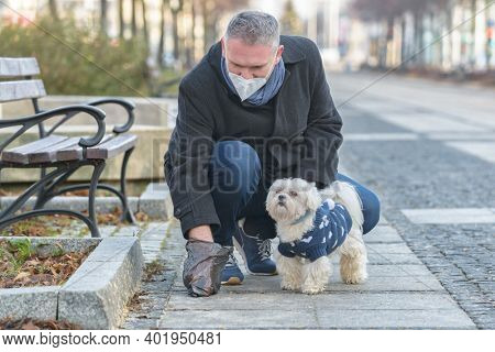 Mature man wearing a protective mask collects dog poop into a bag while walking down a city street