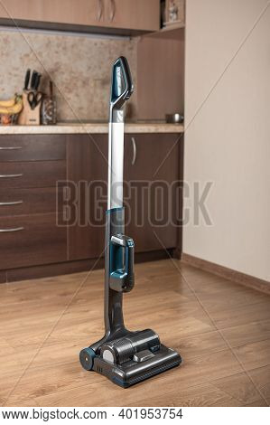 Cordless Handheld Vacuum Cleaner. On The Wooden Floor Against Background Blurry Kitchen. Modern Wire