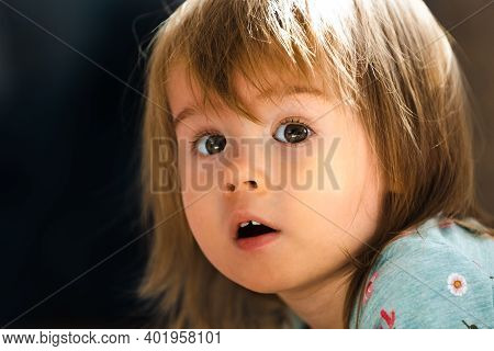Partrait Of 1-2 Year Old Beautiful Girl Looking At Camera Slightly Amazed. Child Expression Concept.