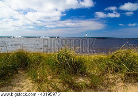 Sunny Summer Day On The Coast Of A Lake Michigan Beach With The Frankfort Lighthouse At The Horizon.