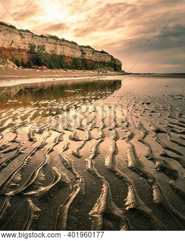 Sand Textures At Low Tide In Hunstanton Beach At Sunrise Behind Red Cliffs