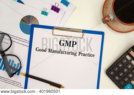 Paper With Gmp Good Manufacturing Practice On The Office Table, Calculator And Office Accessories.