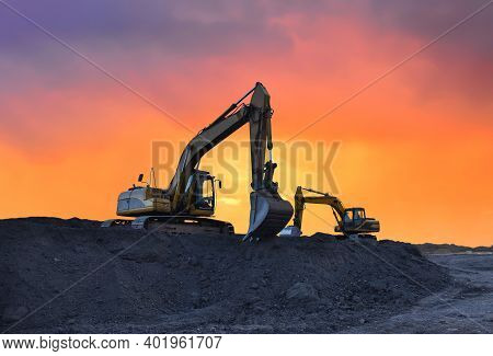 Excavator Working On Earthmoving At Open Pit Mining On Amazing Sunset Background. Backhoe Digs Sand