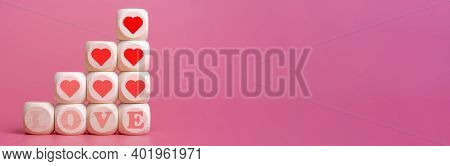 The Word Love And Hearts On Wooden Cubes, Pink Background.