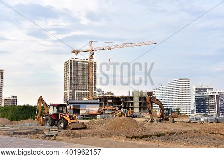 Large Construction Site With Tower Cranes In Action And Earthmoving Equipment. Construction Of New M