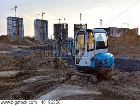 Mini Excavator During Earthmoving At Construction Site On Sunset Background. Onstruction Machinery.