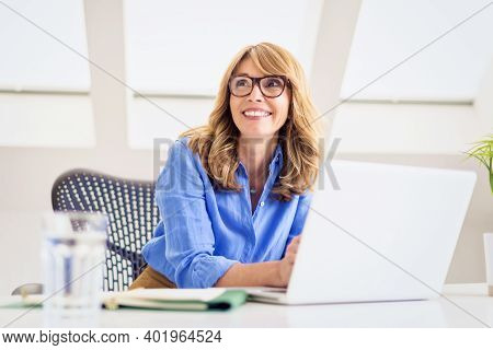 Shot Of Happy Mature Woman Sitting At Desk And Using Her Laptop While Working From Home. Home Office