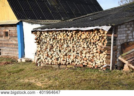 Chopped Logs Of Firewood Piled Under The Roof In The Village In A Backyard. Fuel For Stove Heating.