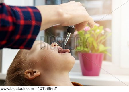 Mother Giving Vitamin Drops With Dropper To Her Child. Dietary Supplements For Kids