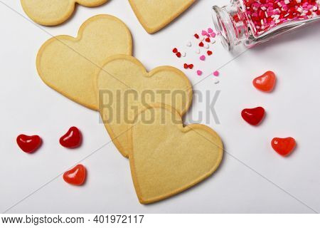 Valentines Day Concept: Fresh baked heart shaped cookies ready for decorating with candy hearts.
