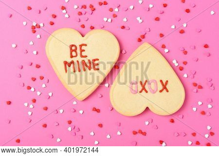 Valentines Day Concept: Two Heart shaped sugar cookies on pink  Be Mine and XOXO written in icing, surrounded by heart shaped sprinkles.