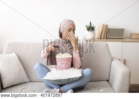 Young Black Woman In Hijab Watching Scary Movie, Covering Her Mouth In Horror, Eating Popcorn On Sof