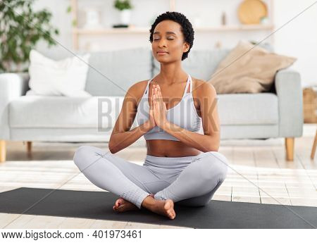Reaching Inner Peace And Harmony. Positive Black Woman Meditating With Closed Eyes, Doing Breathing