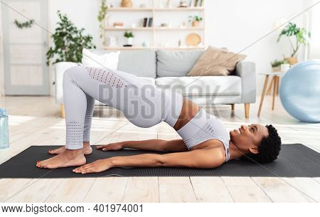 Side View Of Athletic Black Lady Doing Abs Exercise, Standing In Yoga Pose During Her Home Workout.
