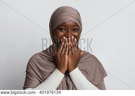 Laughter. Positive Black Muslim Woman In Hijab Covering Mouth With Hands, Feeling Happy Excitement,