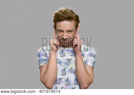 Funny Teenage Boy Grimacing On Gray Background. Close Up Teen Boy Making Funny Grimace.