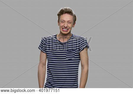 Emotional Teenage Boy On Gray Background. Portrait Of Nervous Expressive Teen Boy. Emotions, Express