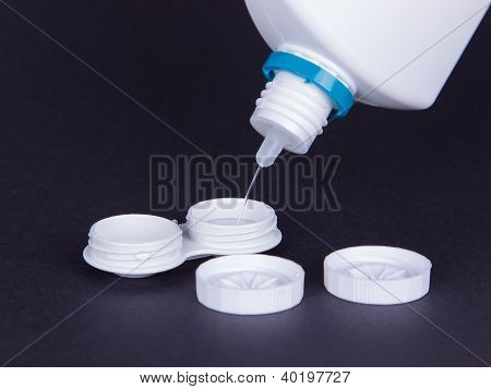 Lens Casing And Bottle Of Water Isolated On Black