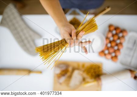 Female Hand Holding Uncooked Spaghetti Above Ingredients On A Table