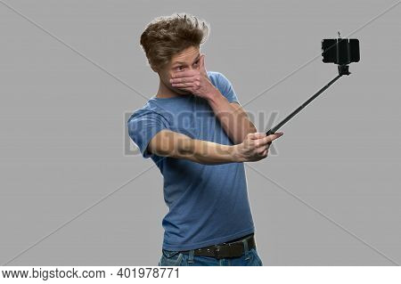 Funny Teen Boy Taking Selfie With Selfie Stick. Boy Using Monopod Standing Against Gray Background.