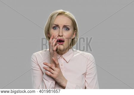 Portrait Of Young Frightened Blonde Woman. Shocked Scared Woman Holding Hands Near Face. Facial Expr