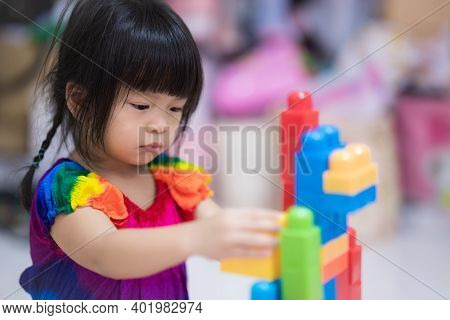 Cute Little Girl Playing Plastic Block. Children Play Plastic Puzzles, Strengthen Imagination And Ha