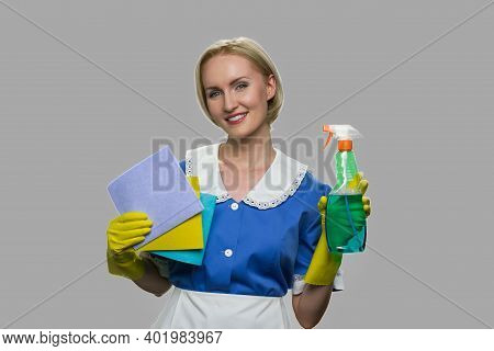 Housekeeper In Uniform Holding Cleaning Supplies. Pretty Smiling Chambermaid With Rags And Detergent