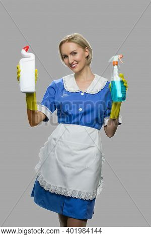 Woman Maid Holding Two Bottles Of Detergent. Smiling House Maid Showing Cleaning Products On Gray Ba