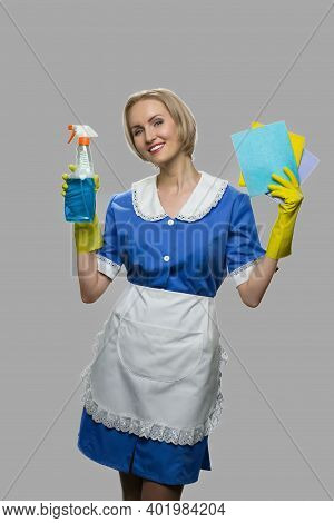 Cheerful Maid In Uniform Holding Rags And Detergent. Smiling House Maid Posing With Cleaning Equipme