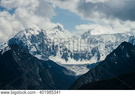 Awesome Scenery With Huge Glacial Mountains. Blue Hole In Cloudy Sky Above Mountain With Glaciers In