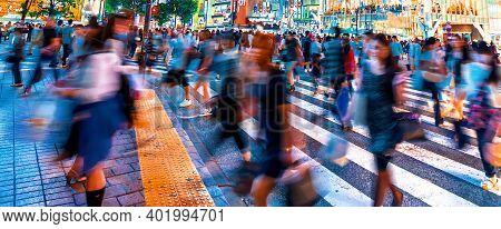 People And Traffic Cross The Famous Scramble Intersection In Shibuya, Tokyo, Japan, One Of The Busie