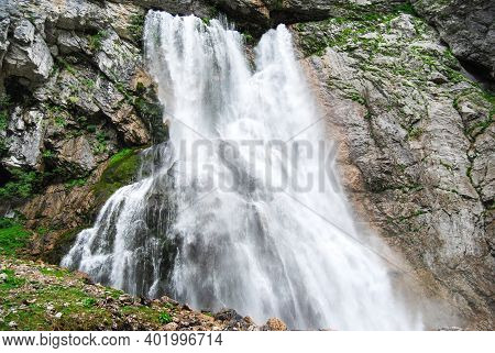Mountain Waterfall. A Powerful Mountain River Bursts Out Of A Mountain Crevice And Falls Like A Wate