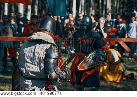 A Knight In Grey Against A Knight With A Wolf On His Shield. Sword Fighting. Imitation Of A Jousting