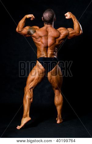 Tanned Bodybuilder Shows Muscles Of Arms And Back