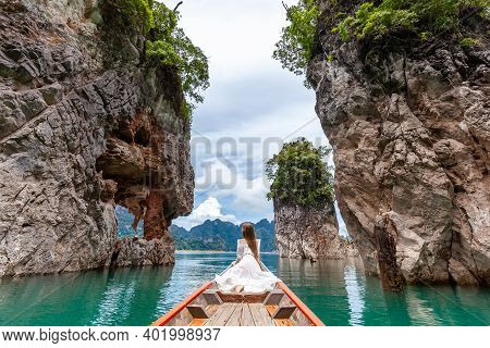 Back View Of Young Female Tourist In Dress And Hat At Longtail Boat Near Famous Three Rocks With Lim