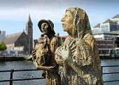 The famine memorial bronze figures on Custom House Quay Dublin Ireland. poster