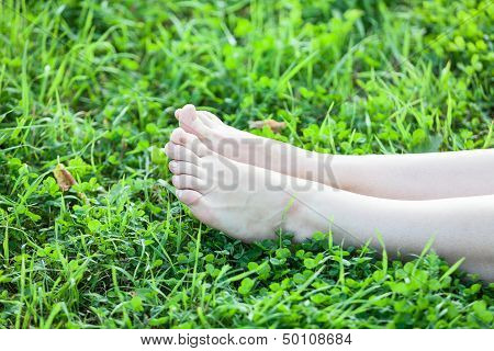 Barefooted Attractive Female Legs Laying In Green Grass