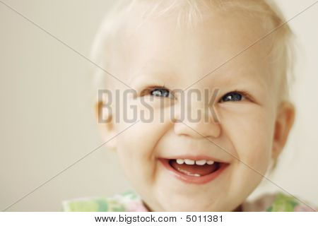 Portrait Of A Smiling And Laughing Toddler.