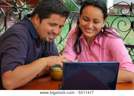 Young Hispanic couple using a laptop computer poster