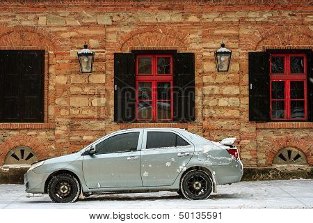 Sports Car Near The Old Building In Winter