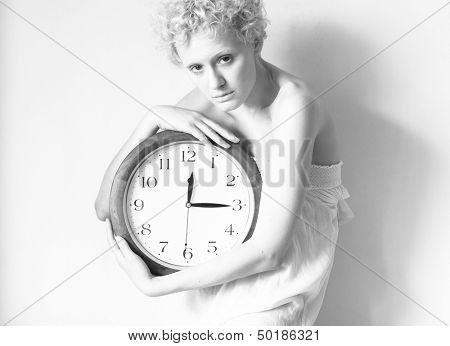 Scrawny blond girl with big clock in hands, black and white photo.
