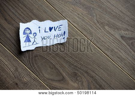 I love you Mom written on piece of paper on a wood background. Space for your text. poster